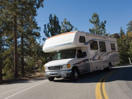 A large white and gray RV driving down a road