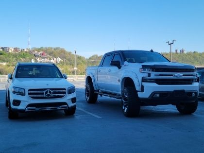 A small car and a large truck parked in a parking lot. Both are white.