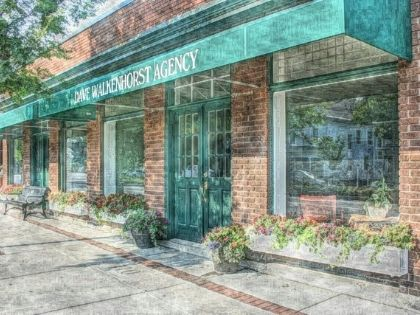 The Dave Walkenhorst Insurance Agency. It is a brick building with a green sign reading Dave Walkenhorst Agency.