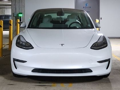 A white sports car parked in a parking garage.