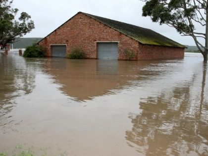 A brick home that is almost completely submerged in flood waters