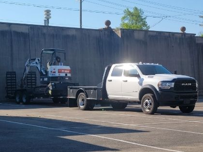 A work truck with a flatbed trailer attached.