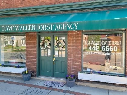 The front of the Dave Walkenhorst Insurance Agency. It is a brick building with green accents and a awning with the business name printed on it.