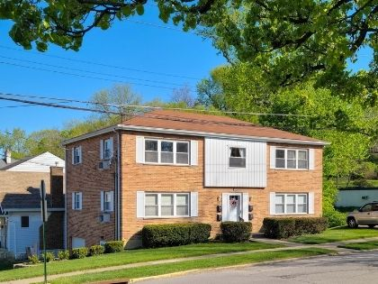 A two story brick rental property in a residential neighborhood.