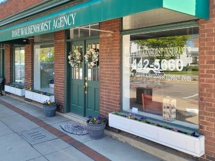 The store front of the Dave Walkenhorst Insurance Agency. It is a brick building with green accents.