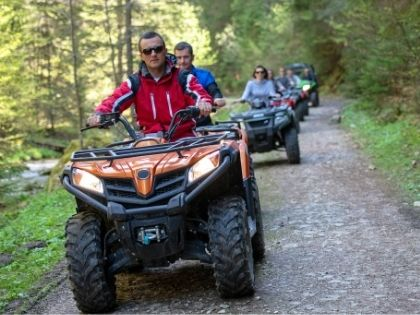 A large group of friends riding ATVs down a rural gravel trail.
