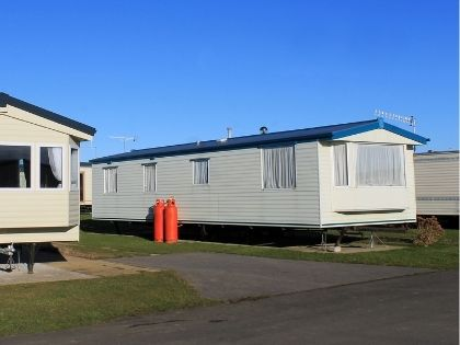 A lot full of single wide mobile homes with white siding.