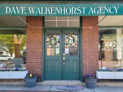 The outside store front of the Dave Walkenhorst Insurance Agency. It is a brick building with green accents and a sign with the business' name