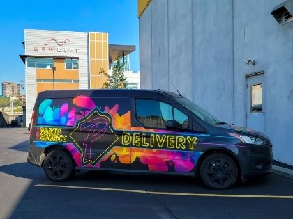 A work van used in deliveries. The van is painted to look like it's been splashed with rainbow paint.